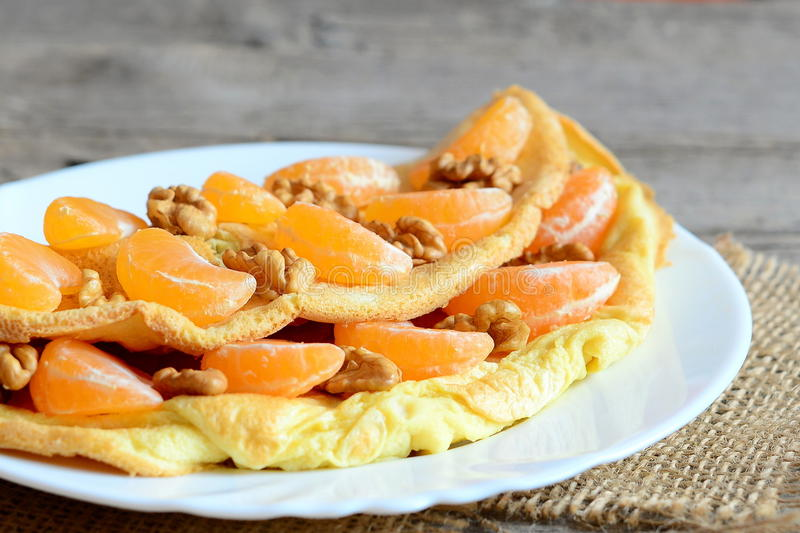 Söt och smaklig omelett på en platta Hemlagad stekt omelett som är välfylld med nya mandariner och rå valnötter på en platta royaltyfria foton