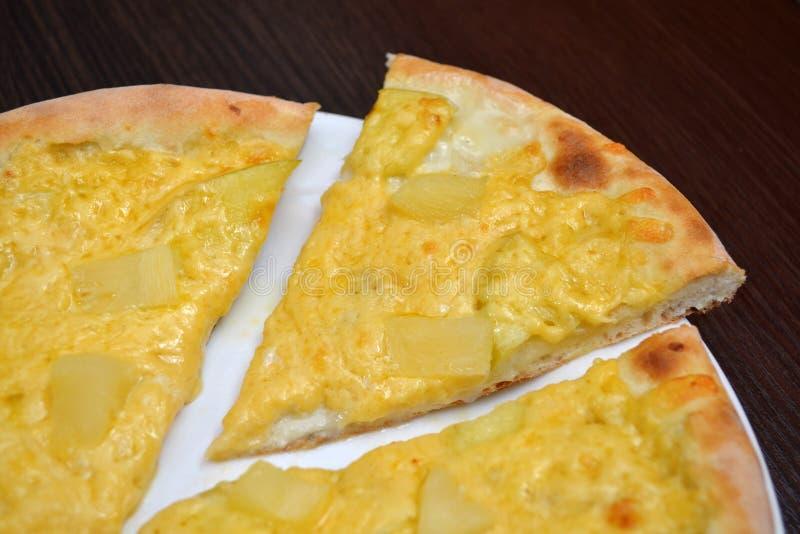 Söt pizza med ost som kondenseras mjölkar, äpplen, och ananors på en vit platta på den mörka trätabellen, ett stycke klipper av fotografering för bildbyråer