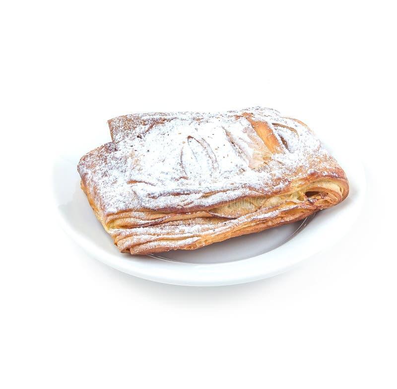 Söt smördegbulle som täckas med sockerpulver på en vit platta på vit bakgrund royaltyfri fotografi
