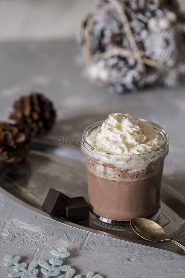 Söt varm choklad med kräm och skivan av mörk choklad i exponeringsglas på magasinet på konkret bakgrund arkivfoto