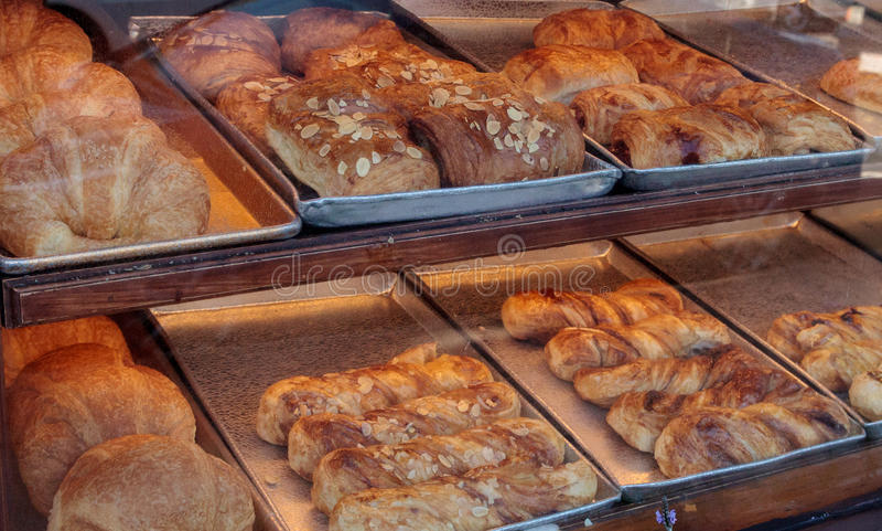 Söta bakelser i bagerifönster royaltyfria foton