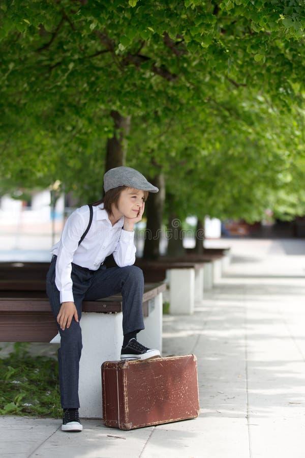 Söta barn i vintage-kläder, hatt, suspensioner och vita skjortor, med resväska, som löper i parken fotografering för bildbyråer