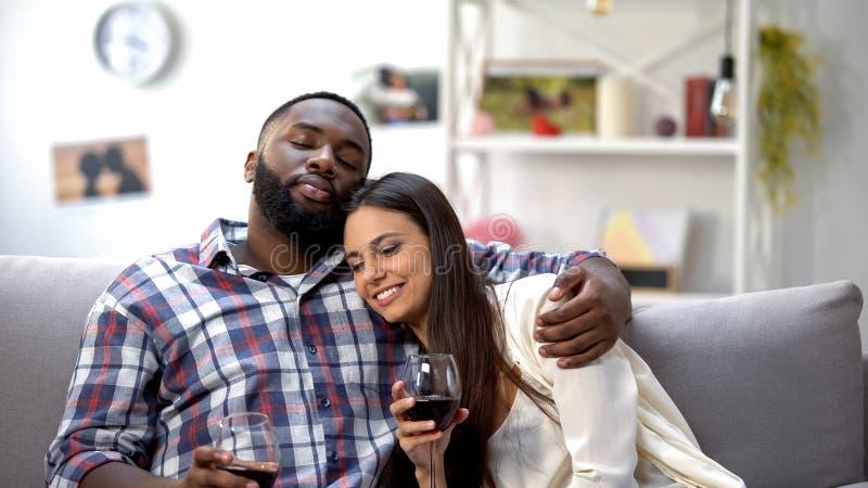 Söta blandad-lopp par som hemma kramar och kopplar av med vin, fritid royaltyfri bild