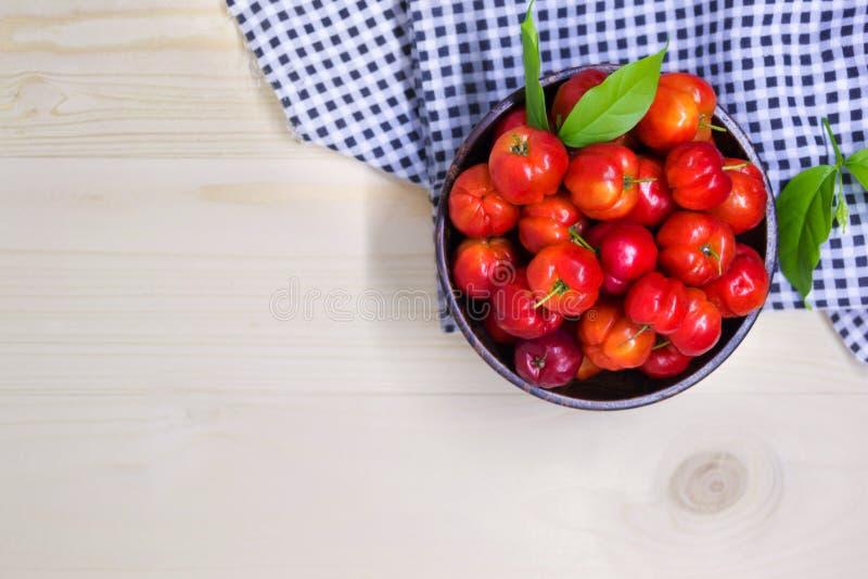 Söta Cherry Berries In Wooden Bowl med tartantyg arkivfoton