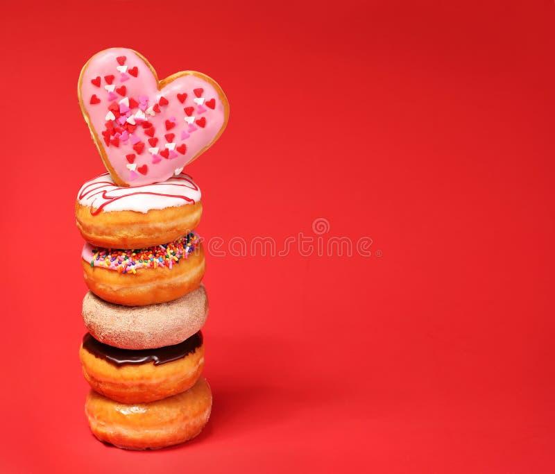 Söta donuts med hjärta formade munken på överkanten över rött royaltyfri bild