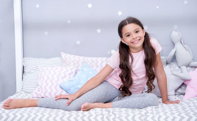 Söta drömmar för önska Flickabarnet sitter på säng i hennes sovrum Ungen förbereder sig att gå att bädda ned Angenäm tid i hemtre royaltyfri foto