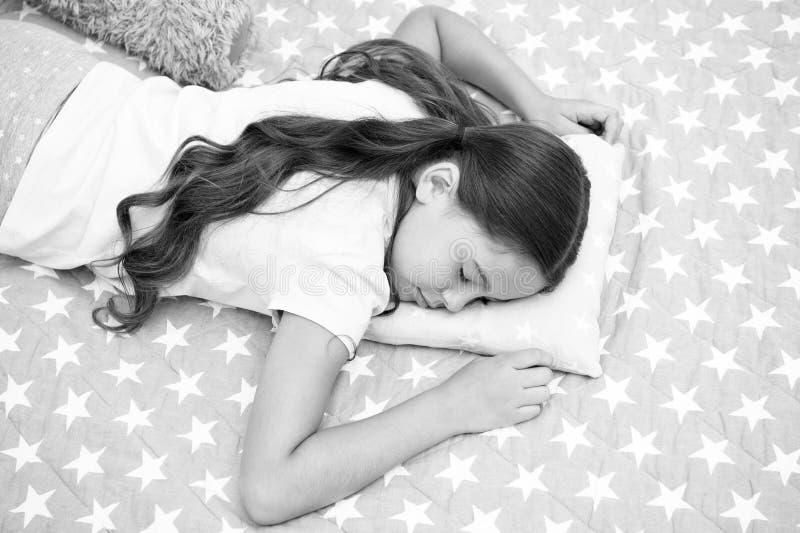 söta drömmar Faller långt hår för flickabarnet sovande på kuddeslut upp Kvalitet av sömn beror på många dela upp i faktorer välj royaltyfria bilder