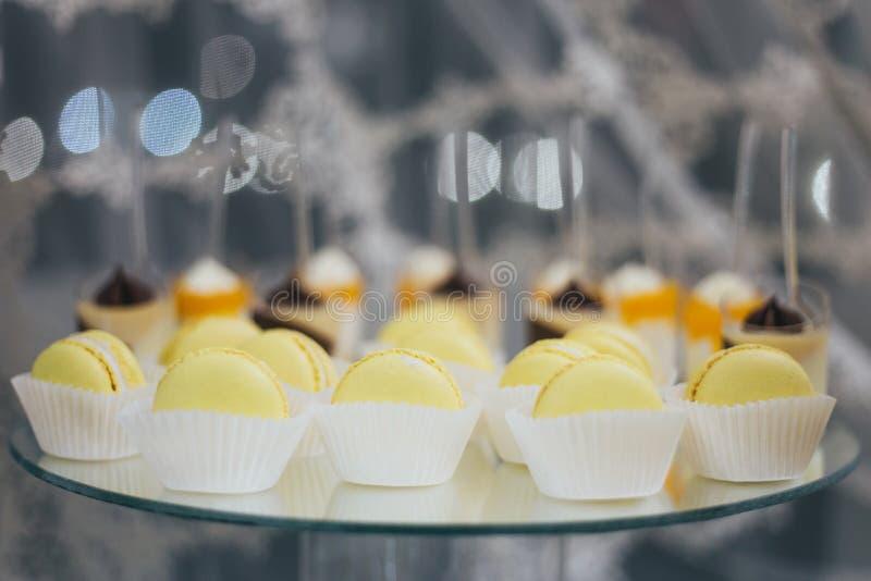 Söta färgrika macarons som isoleras på den dekorerade tabellen arkivfoto