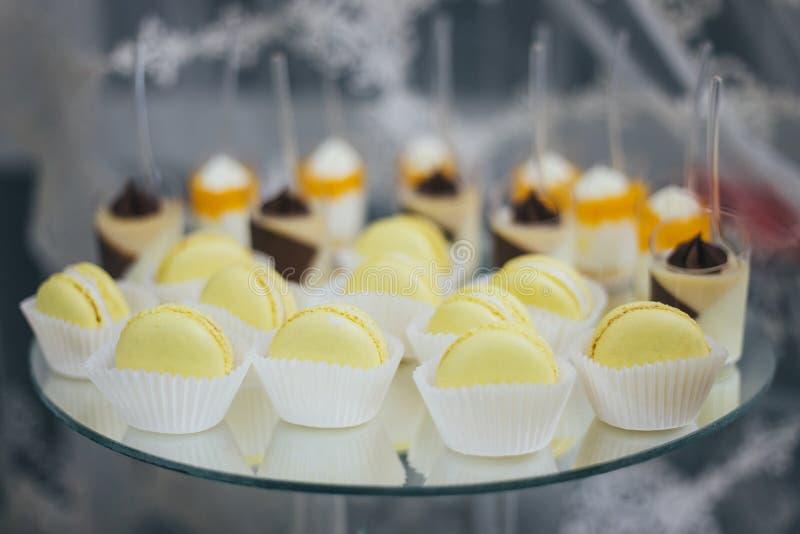 Söta färgrika macarons som isoleras på den dekorerade tabellen royaltyfri bild