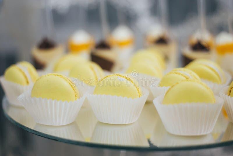 Söta färgrika macarons som isoleras på den dekorerade tabellen royaltyfri foto