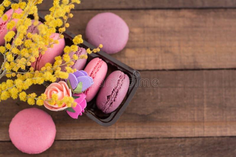 Söta franska macarons i en packe med blommor och mimosan royaltyfri fotografi