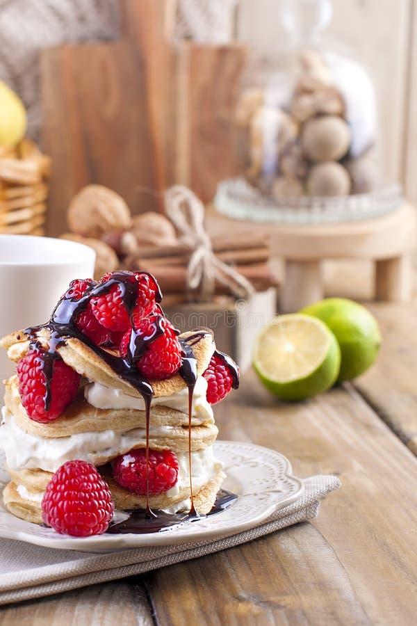 Söta hem- punkcakes med vitkräm och nya bär för rött hallon Två exponeringsglas av te för frukost och en kokkärl på ett trä arkivfoton