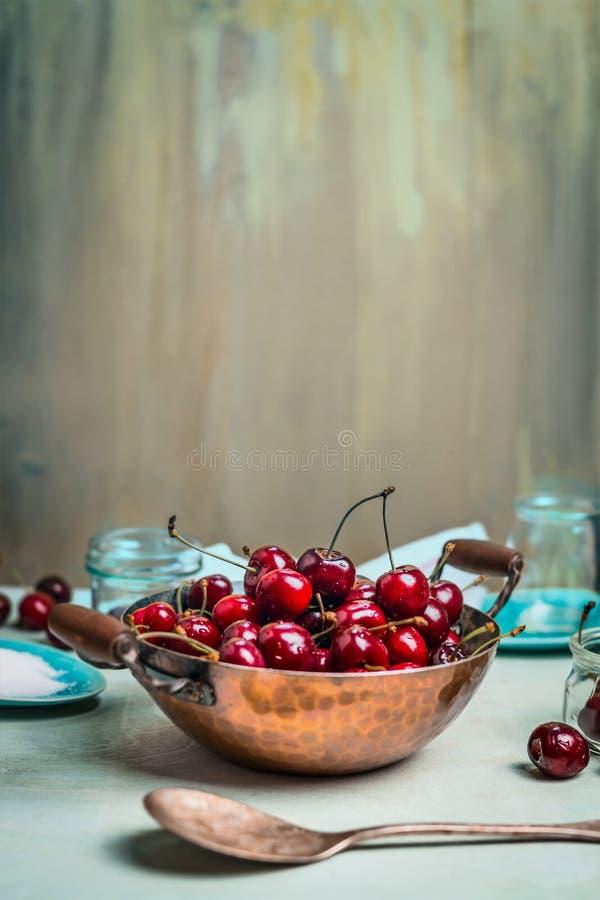 Söta körsbär i gammal kopparkruka med den glass krus och skeden på ljus - blå lantlig träbakgrund royaltyfria foton