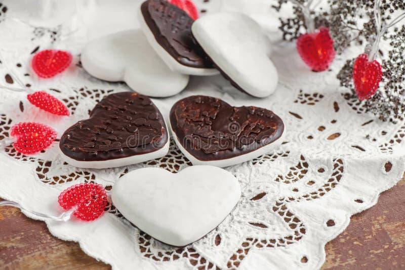 Söta kakor i form av hjärtor från pepparkakadegchoklad och en vit glasyr traditionella kakor arkivfoton