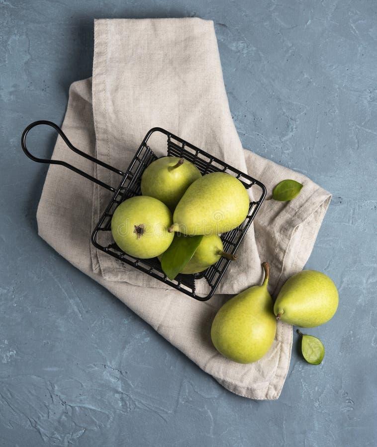 Söta läckra gröna päron inom svart korg på den blåa tabellfrukten royaltyfria foton