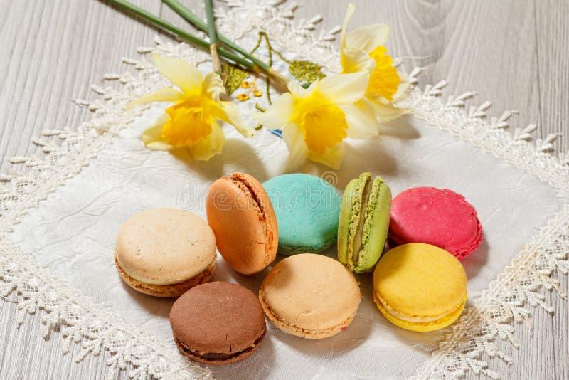 Söta macaronskakor av olik färg på siden- servett med bouq arkivfoton