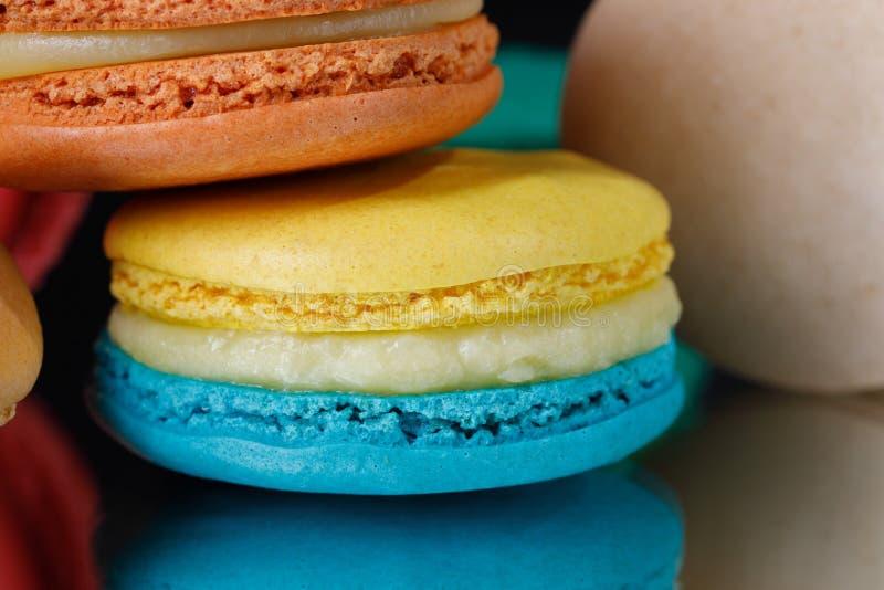 Söta och färgglade franska makron eller macaron på svart bakgrund arkivfoton