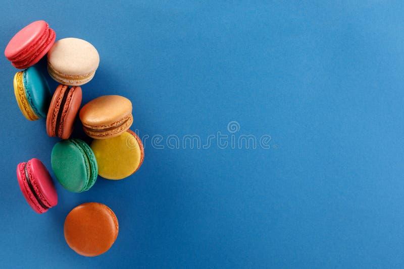 Söta och färgrika franska makron på blå bakgrund Efterrätten är med te eller kaffe arkivfoto