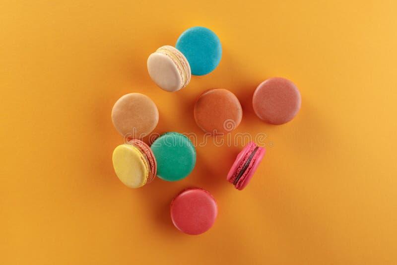 Söta och färgrika franska makron på en gul bakgrund Efterrätten är med te eller kaffe fotografering för bildbyråer