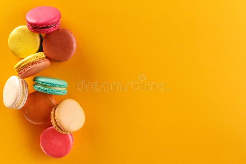 Söta och färgrika franska makron på en gul bakgrund Efterrätten är med te eller kaffe royaltyfri fotografi