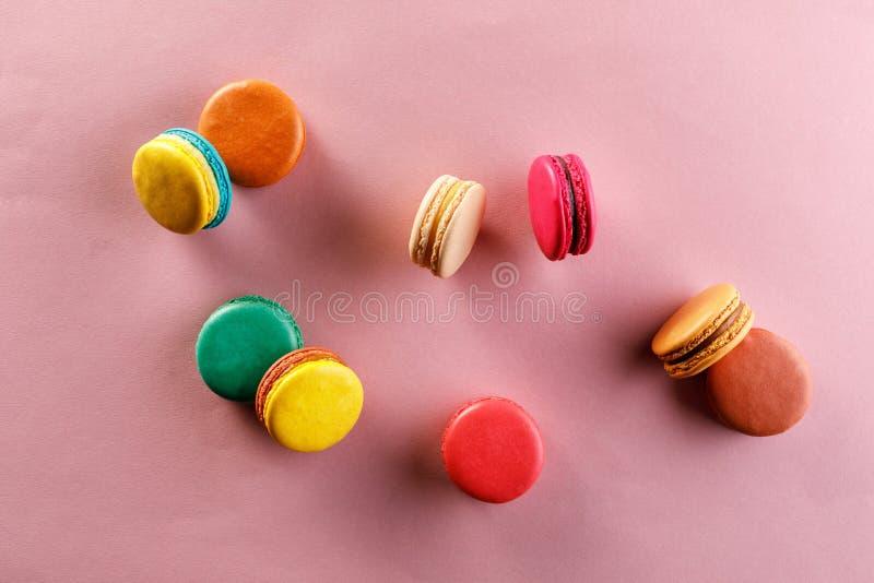 Söta och färgrika franska makron på en rosa bakgrund Efterrätten är med te eller kaffe arkivfoto