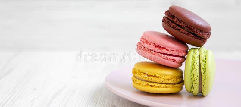 Söta och färgrika macarons på en rosa platta över vit träbakgrund, sidosikt kopiera avst?nd arkivbilder