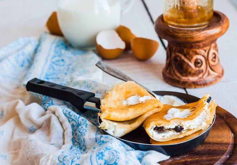 Söta pannkakor med keso, katrinplommoner, honung i ett steka p royaltyfri fotografi
