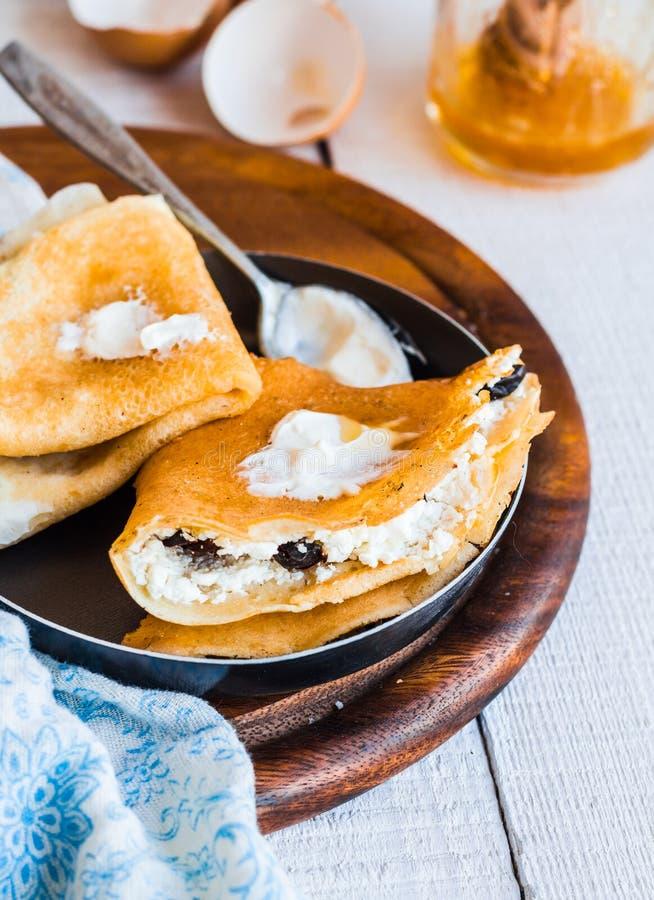 Söta pannkakor med keso, katrinplommoner, honung i ett steka p royaltyfria foton