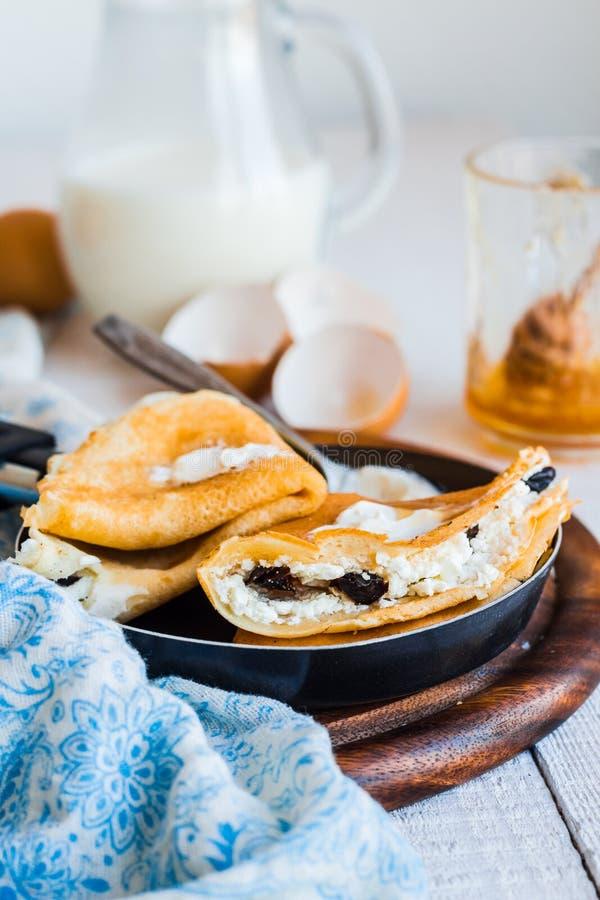 Söta pannkakor med keso, katrinplommoner, honung i ett steka p arkivfoton