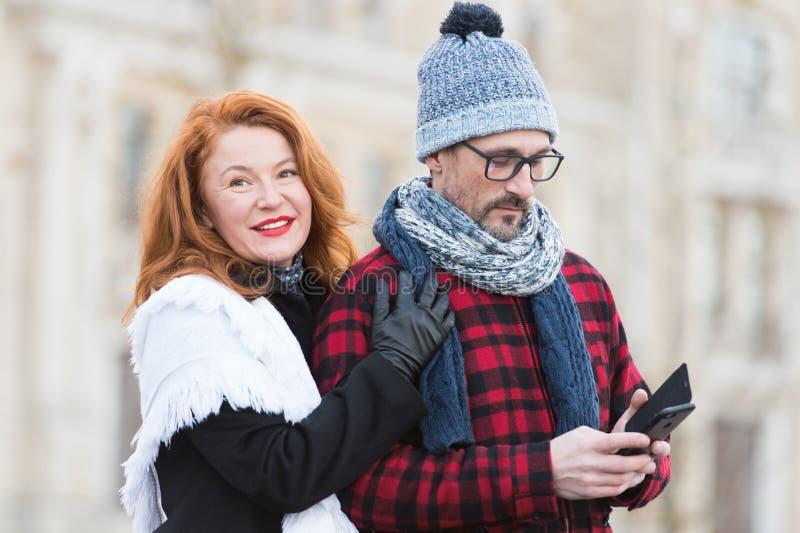 Söta par med den smarta telefonen i händer Man med Smart-telefonen i hand och le kvinna royaltyfria foton
