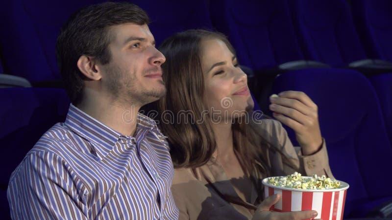 Söta par som håller ögonen på romantisk komedi på bion arkivbild
