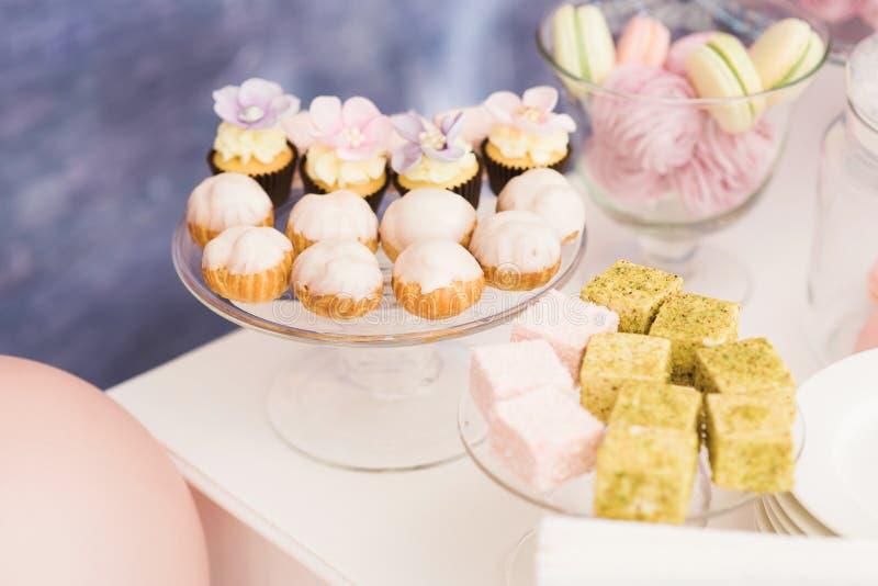 Söta produkter på ett bröllop Smakliga kakor och kakor på glasswar arkivbild