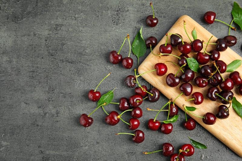 Söta röda körsbär på träbräde arkivbild