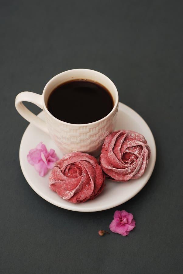 Söta rosa marängar och kopp kaffe på bakgrund för blåa grå färger med rosa blommor Vårbakgrund med kopieringsutrymme frukost arkivbild