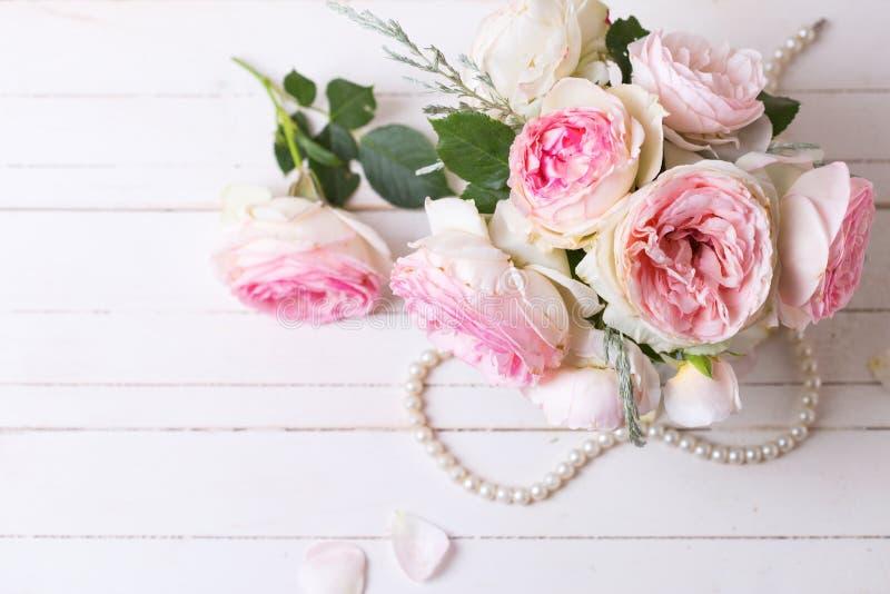 Söta rosa rosor blommar på vit målad träbakgrund arkivfoton