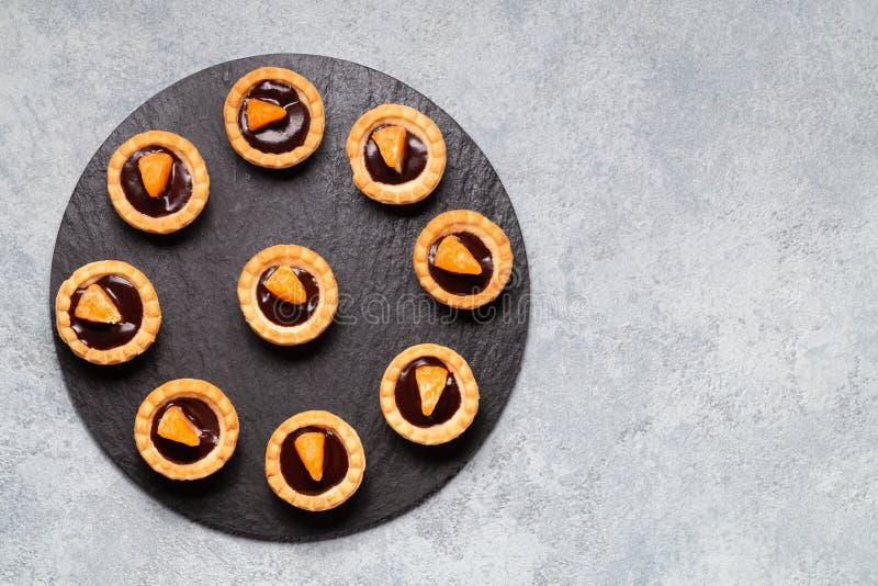 Söta tartlets med choklad och skivor av tangerin på en maträtt av naturligt kritiserar för att tjäna som, bästa sikt royaltyfri foto