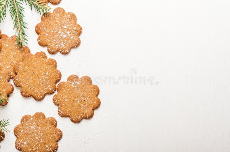 Söta tunna ljust rödbrun kakor på vit bakgrund med pudrade socker- och granfilialer Festlig bakelse, julafton Bästa sikt, Co royaltyfri bild