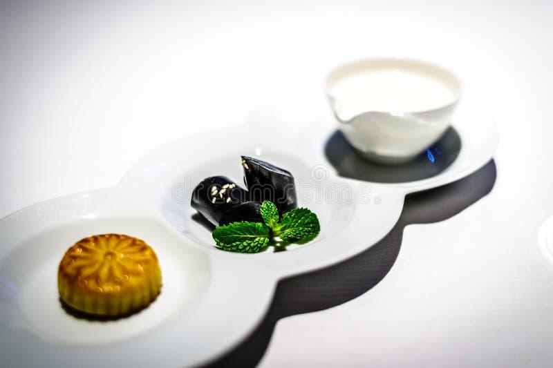 Sötad mandelkräm med äggvita sötad svart sesam rullar bakade vaniljsåssmördegar med kokosnötfruktsaft arkivbilder