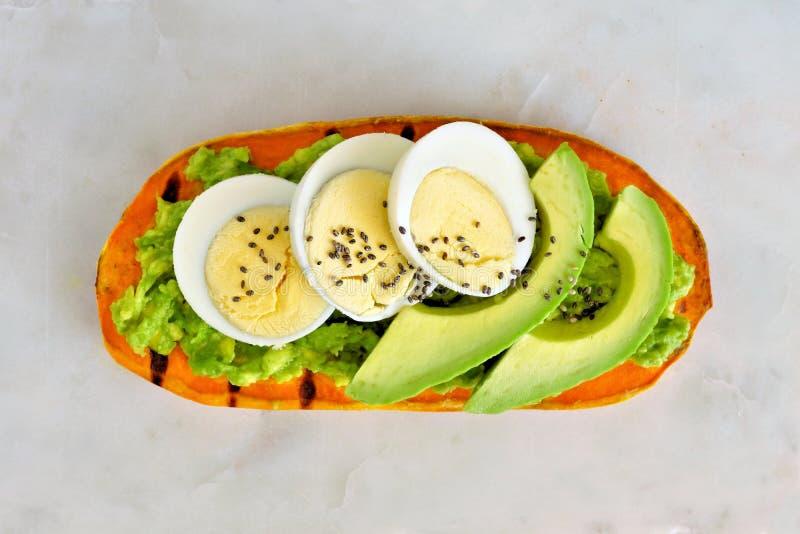 Sötpotatisrostat bröd med avokadot, ägg och chiafrö över marmor fotografering för bildbyråer