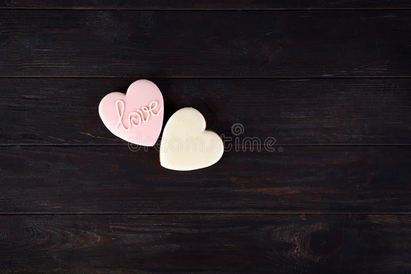 Sötsaker på dag för valentin` s Kakor i form av hjärta och med att märka förälskelse på mörk träkopia för bästa sikt för bakgrund fotografering för bildbyråer