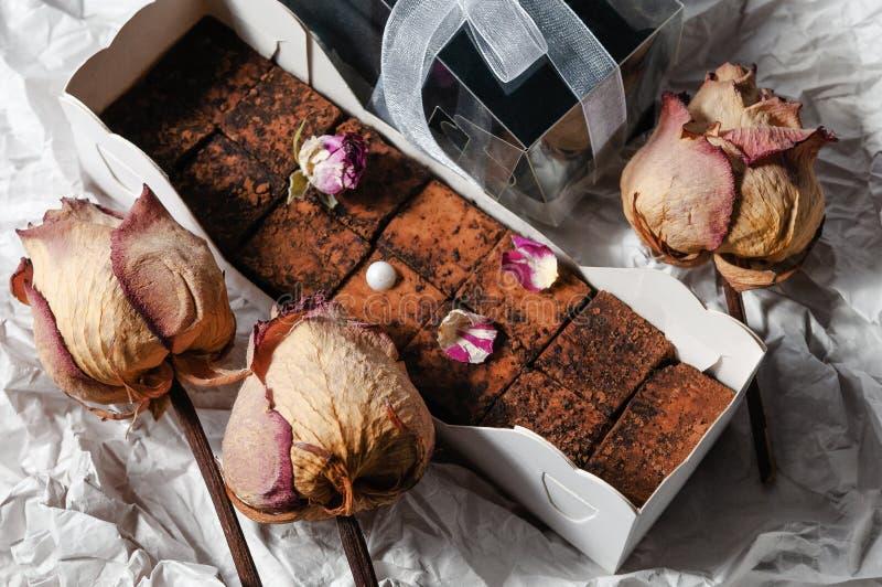 Sötsaker som göras från mjukt soufflé- och kakaopulver I den original- kartongen Dekorerat med rosa kronblad och pärlan arkivbilder