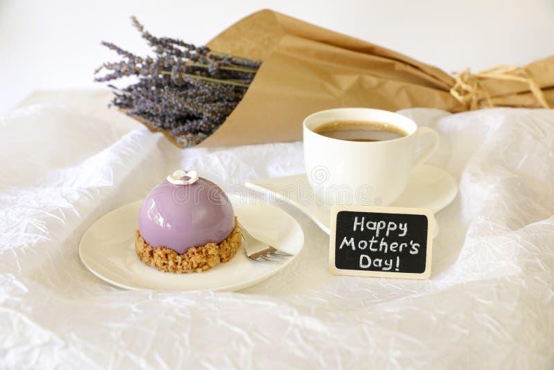Sött begrepp för morgonfrukosttid, härlig violett kaka, near platta för kopp kaffe med för moder` s för anmärkning den lyckliga d royaltyfri bild