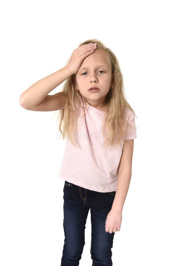 Sött gulligt litet kvinnligt barn som trycker på hennes head lidandehuvudvärk som ser trött och ledsen arkivfoto