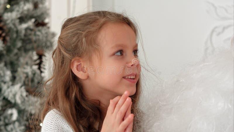 Sött liten flickasammanträde på att beskriva för Santa Claus varv vilka gåvor hon önskar för jul royaltyfria bilder