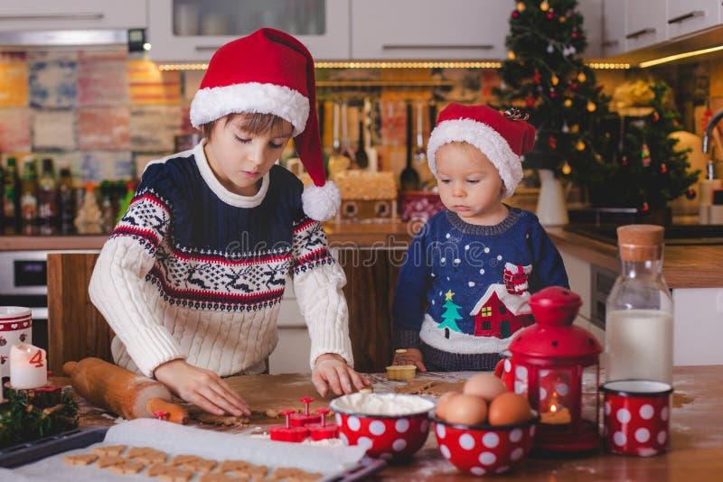 Sött litet barnbarn och hans äldre broder, pojkar, hjälpande mamma p royaltyfria foton