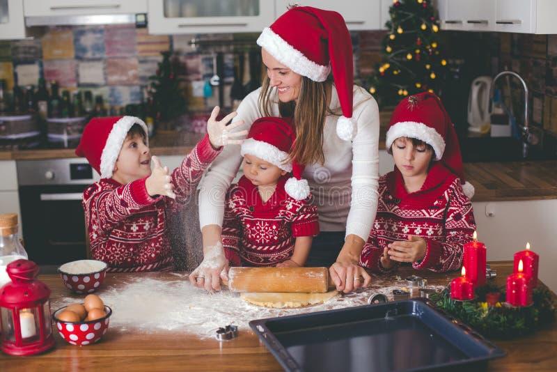 Sött litet barnbarn och hans äldre broder, pojkar, hjälpande mamma som hemma förbereder julkakor royaltyfri fotografi