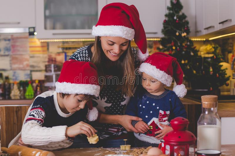 Sött litet barnbarn och hans äldre broder, pojkar, hjälpande mamma som hemma förbereder julkakor royaltyfria bilder