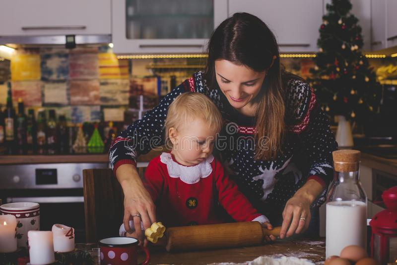 Sött litet barnbarn, pojke, hjälpande mamma som förbereder julkocken royaltyfri fotografi