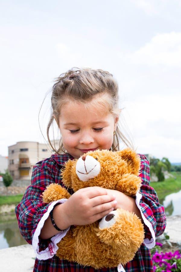 Sött litet innehav hans nallebjörn i henne armar royaltyfri fotografi
