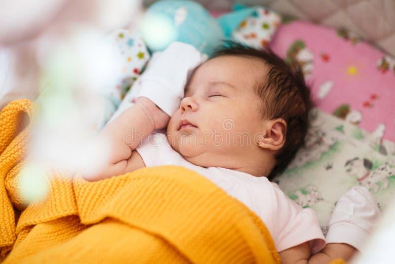 Sött nyfött behandla som ett barn flickan sover i hennes lathund arkivbild